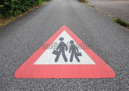 schild auf asphaltstrasse mit schule oder