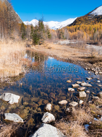 small alpine mountain pond in fall