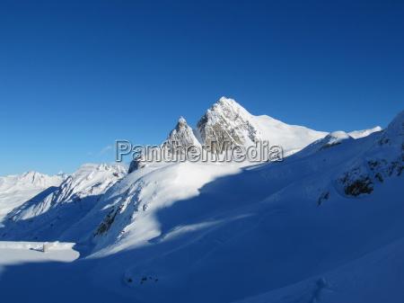 winteralpine bergszene unter blauem himmel