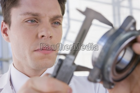 close up of serious engineer measuring