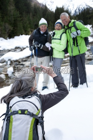 woman photographing senior friends with ski