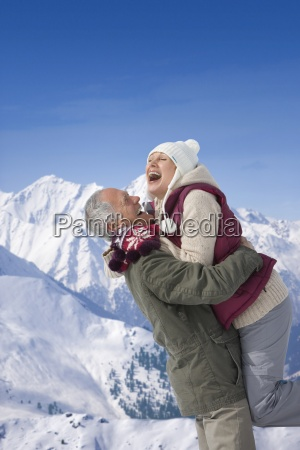 senior man lifting woman on snowy