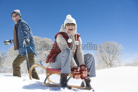 portrait of smiling senior couple sledding