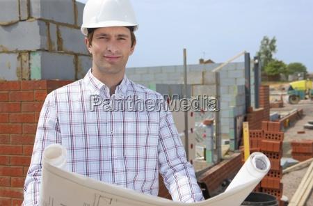 portrait of smiling architect holding blueprints