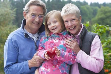 portrait of smiling grandparents and granddaughter