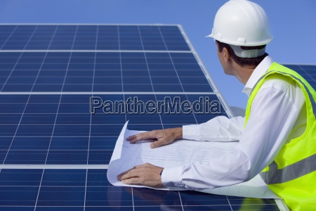 engineer with blueprint inspecting solar panels