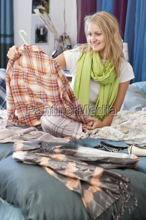 young woman looking at shirt in