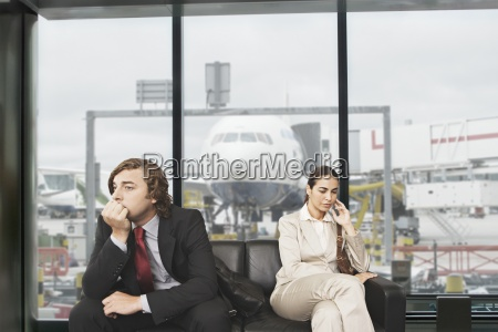 serious businessman and businesswoman waiting in