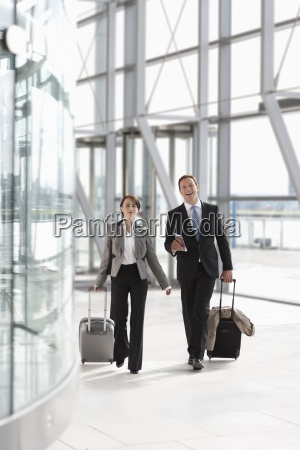 businessman and businesswoman pulling suitcases in