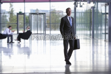 smiling businessman walking with briefcase in