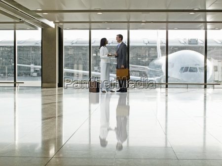 business people talking together in airport