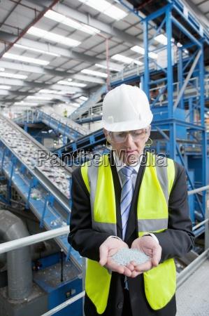 businessman examining plastic pellets in recycling