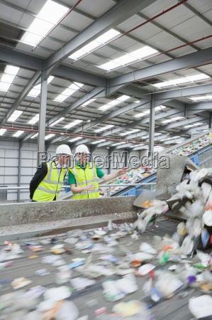 businessman and worker watching plastic on