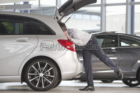 man looking into hatchback of car