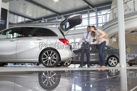 salesman and customer looking into hatchback