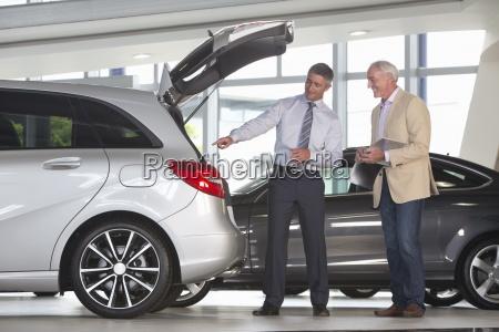 salesman and customer with brochure looking