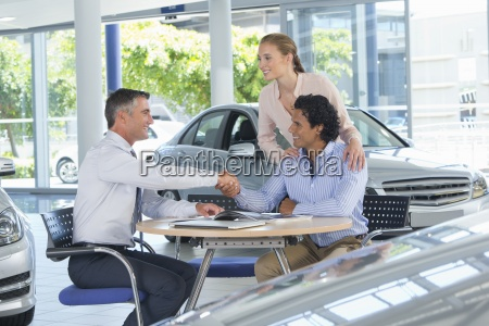 salesman and couple shaking hands at