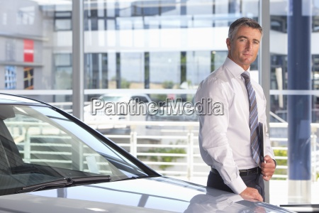 portrait of confident salesman leaning on
