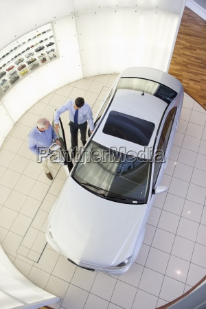 salesman and customer looking inside car