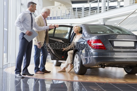 salesman and couple looking at car