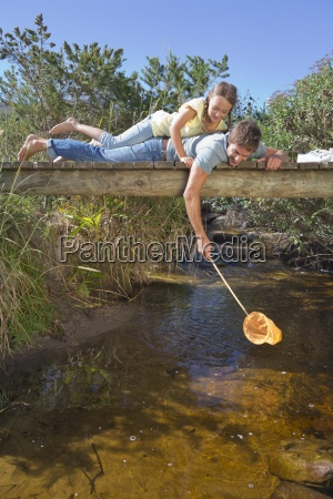 father and daughter laying on footbridge