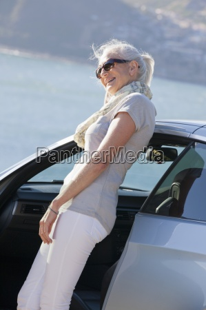 smiling woman leaning against car and