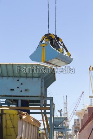 grab bucket unloading grain from bulk