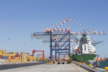 cranes and container ship at commercial