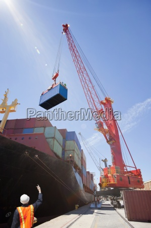 worker guiding crane unloading container ship