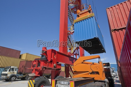 crane lifting cargo container above lorry