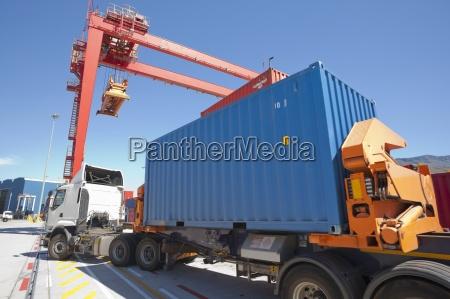 crane loading cargo containers onto lorries