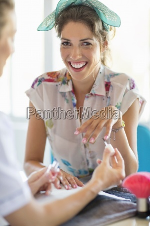 portrait of smiling woman getting manicure