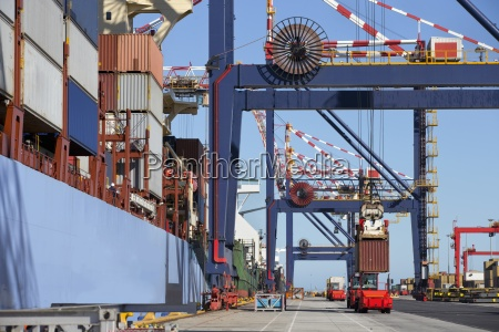 crane loading cargo container onto container