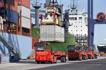 crane lowering cargo container onto truck