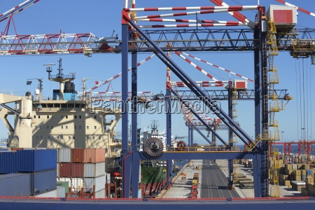 cranes alongside moored container ship at