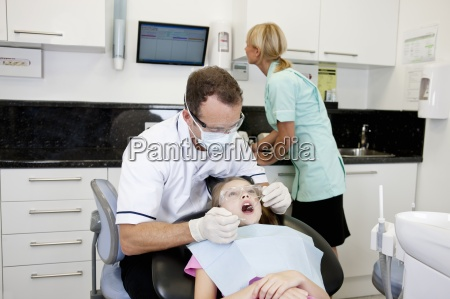 a male dentist examining a young