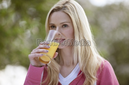 a young woman drinking a glass