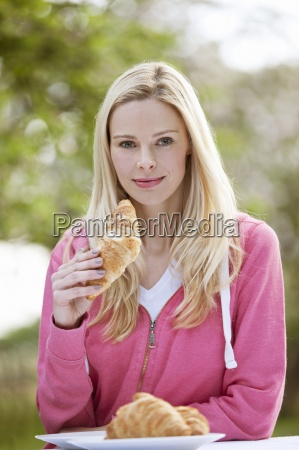 a young woman eating a croissant