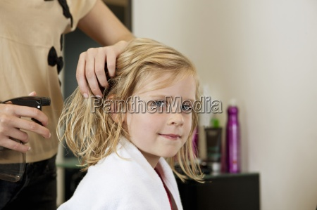 a female hairdresser spraying water on