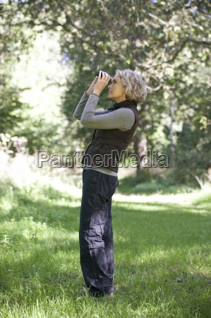 a mature woman outdoors looking through
