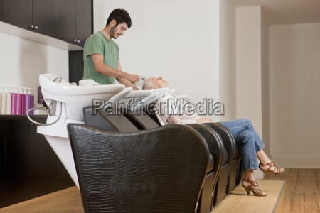 a male hairdresser washing a female