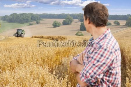 farmer zuschauen zugmaschine und anhaenger in