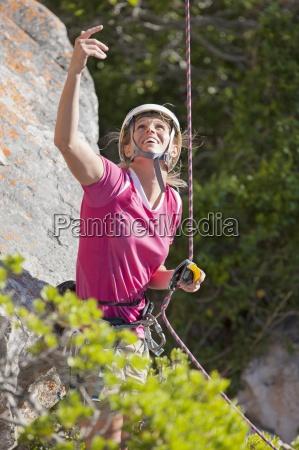 laechelnde weibliche steinbergsteiger sucht und gestikulierend