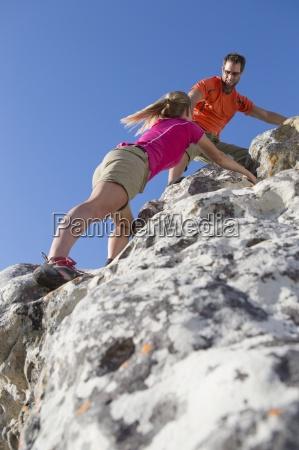 maennlich kletterer hilft frau bis felswand