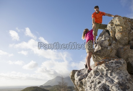 maennlich kletterer hilft frau up felswand