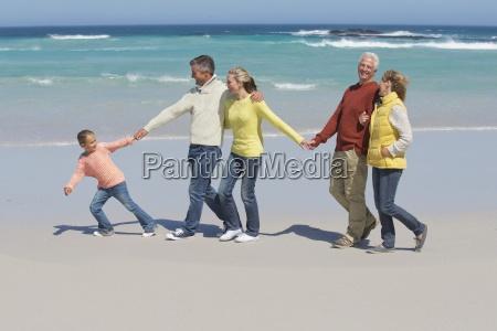 froehliche mehrgenerationen familienwanderung am sonnigen strand