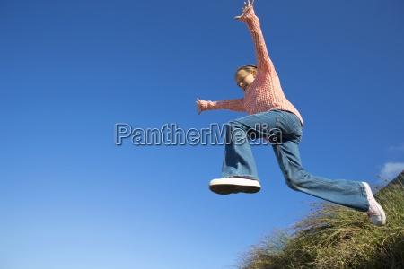begeisterte maedchen springt gegen den blauen