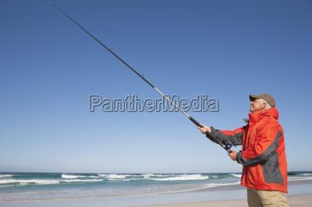 fischen des aelteren mannes am sonnigen