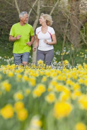 smiling senior couple jogging in sunny