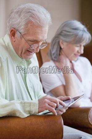aelterer mann mit brille digitalen tablet